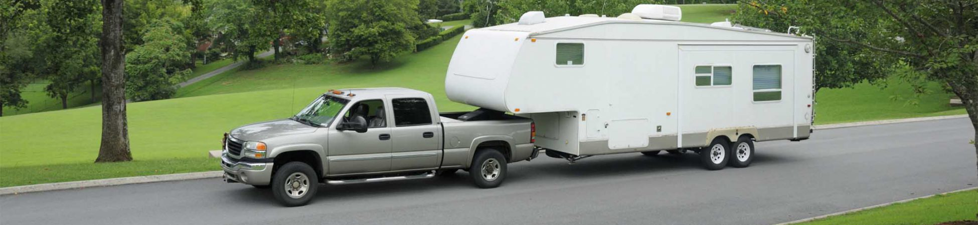 """Recreational vehicle fifth wheel travel trailer being towed by pickup truck, parked on the road in the mountains. Horizontal with copy space above."""